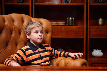 Boy sits in leather armchair in luxury office photo