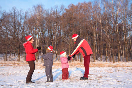 Parents and children in red huts play in wood in winter photo