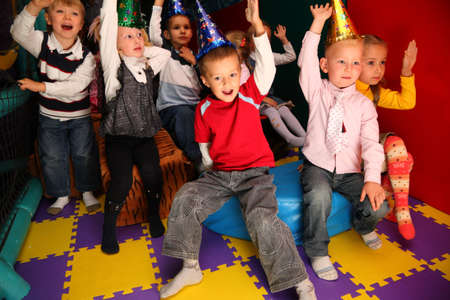 Children on holiday in kindergarten with raised hands photo