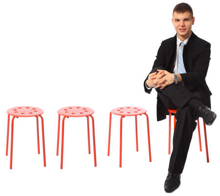 young businessman sits on red stool leg on leg Stock Photo - 5367026