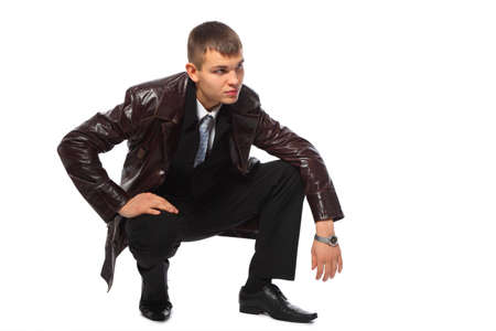 unoccupied: Young businessman in leather jacket squats