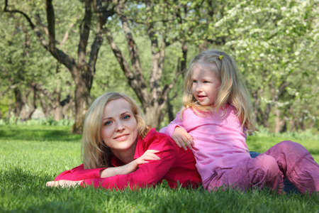 leant: daughter has leant elbows on mother lying on grass in park Stock Photo