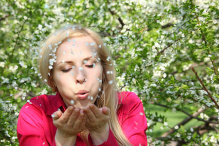Beauty young woman  blowing off petals photo