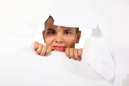 young man looking out in hole in paper photo
