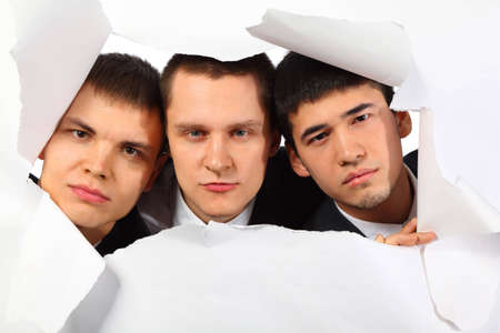 punch holes: Three young men looking out in hole in paper