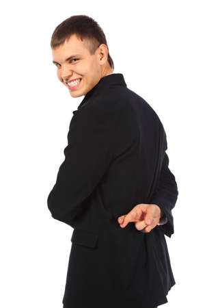 trickery: Smiling businessman with fingers crossed behind his back