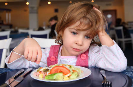 kid sitting: Sad girl behind table in cafe