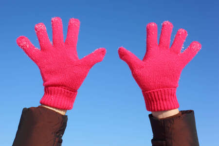 Two hands in red gloves against  blue sky photo