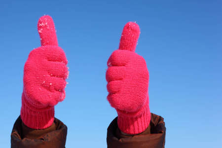Two hands in red gloves against  blue sky show gesture ok photo