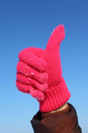 Hand in red glove against  blue sky shows gesture ok  photo