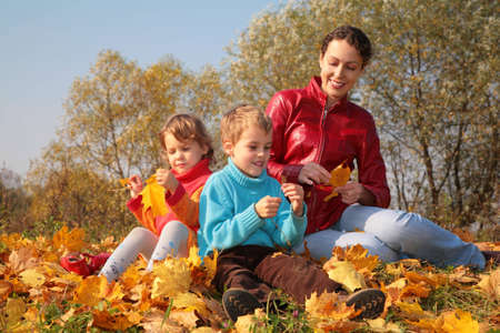 Mother with children sit on fallen maple leaves Stock Photo - 5365561