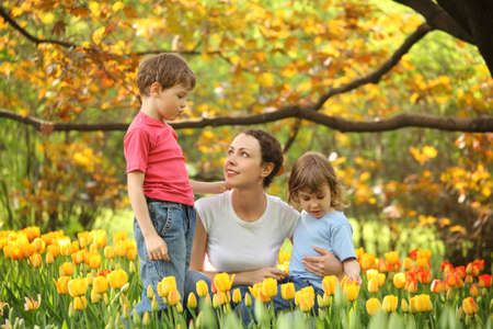 Mother with children in garden in spring among blossoming tulips photo