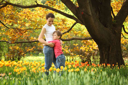 son embraces mother in garden in spring among blossoming tulips photo