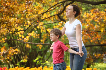 Mother with son to keep for hands in garden in spring photo