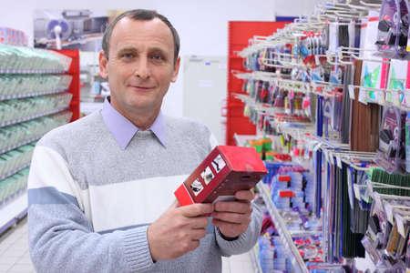 papeteria: starszy pan w sklepie z pudełkiem w rękach