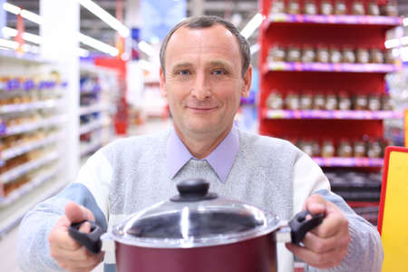 elderly man in shop with pan in hands