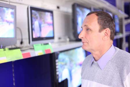 elderly man in shop looks at TVs Stock Photo - 5367074