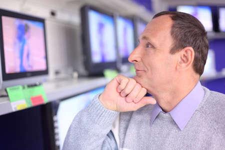 elderly man in shop looks at TV Stock Photo - 5355074
