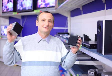 älterer Mann im Shop von Radio-Engineering mit Lautsprechern in den Händen