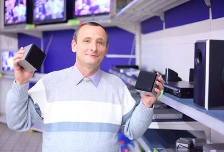 store shelf: elderly man in shop of radio engineering with loudspeakers in hands Stock Photo