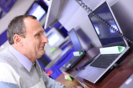 elderly man in shop looks at laptop Stock Photo - 5367200