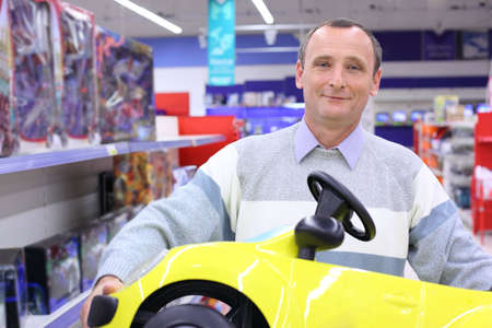 elderly man in shop with children's car in hands Stock Photo - 5367376