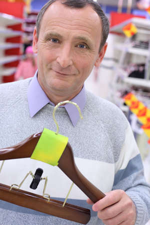 elderly man in shop with hanger for clothes in hands Stock Photo - 5367454