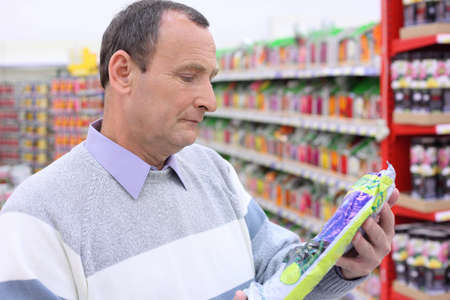 elderly man in shop with package in hands Stock Photo - 5367558