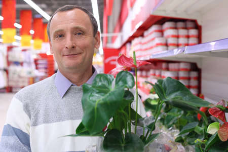 elderly man in shop with  plant in hand Stock Photo - 5365491