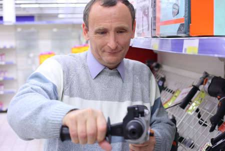 elderly man in shop with drill in hands Stock Photo - 5367682