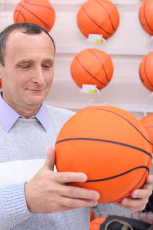 elderly man in shop with basketball ball in hands  photo