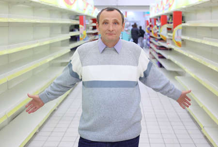 between: elderly man stands between empty shelves in  shop with dissolved  hands  Stock Photo