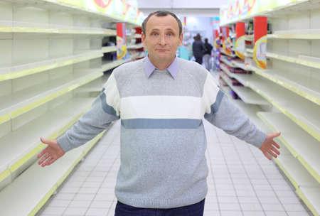 dissolved: uomo anziano si trova tra gli scaffali vuoti in negozio con le mani disciolto