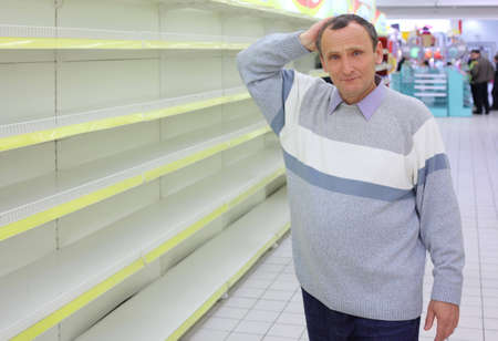 elderly man at empty shelves in  shop scratches in  nape photo