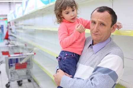 elderly man at empty shelves in  shop with child on hands photo