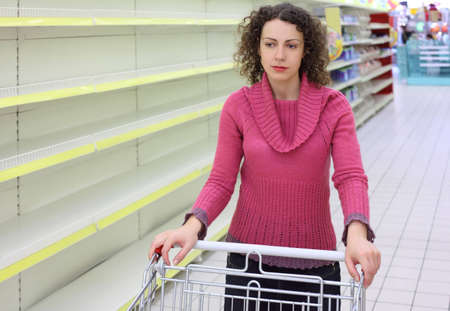 brunt: young woman with  cart in shop with empty shelves