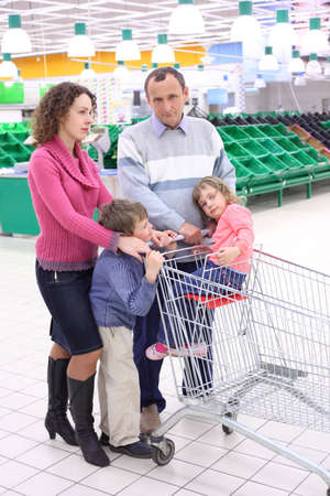 elderly man and  young woman with children in shop with empty shelves photo