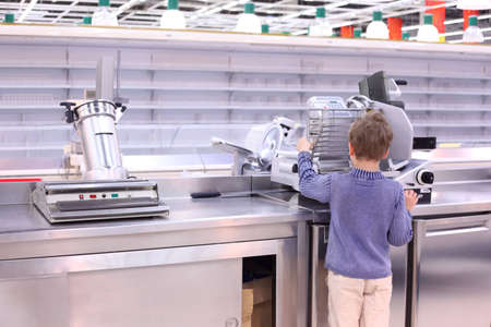 boy stands at slicer in empty shop photo