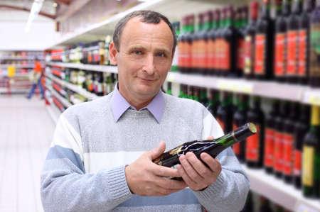 elderly man in shop with wine bottle in hands Stock Photo - 5367728
