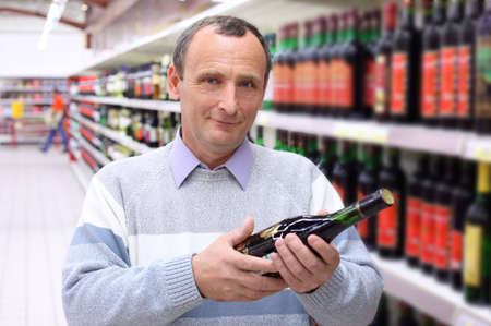 elderly man in shop with wine bottle in hands Stock Photo - 5367728