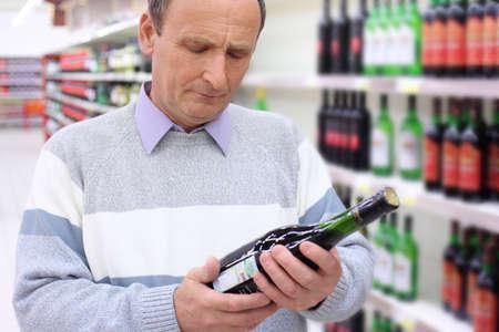 elderly man in shop looks on wine bottle in hands Stock Photo - 5358923