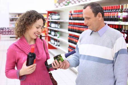 happy girl and  elderly man in shop with wine bottles in hands photo
