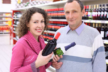 happy girl and  elderly man in shop with wine bottles in hands Stock Photo - 5365405