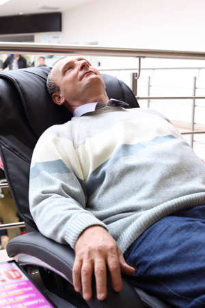 table and chairs: elderly man lies in massage armchair