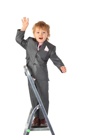 gesticulate: boy in suit balances at step-ladder top