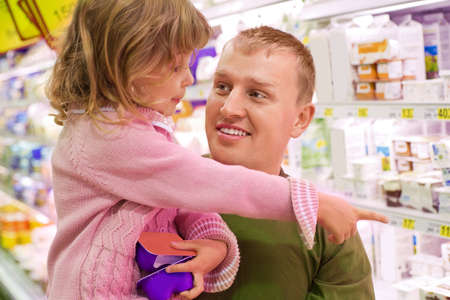 Smiling young man with little girl buy yogurt in supermarket Stock Photo - 7836158