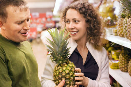 Smiling young man and woman buy pineapple in supermarket Stock Photo - 7836264