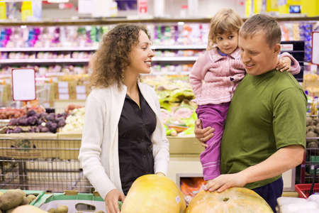 family with little girl  buy pumpkin in supermarket photo