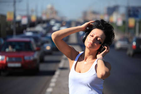 girl listens music in ear-phones on highway middle photo