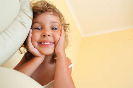 foreshortening: pretty smiling little girl in cosy room, foreshortening from below
